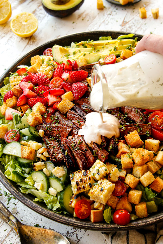 showing how to make steak salad by pouring blue cheese dressing onto the salad