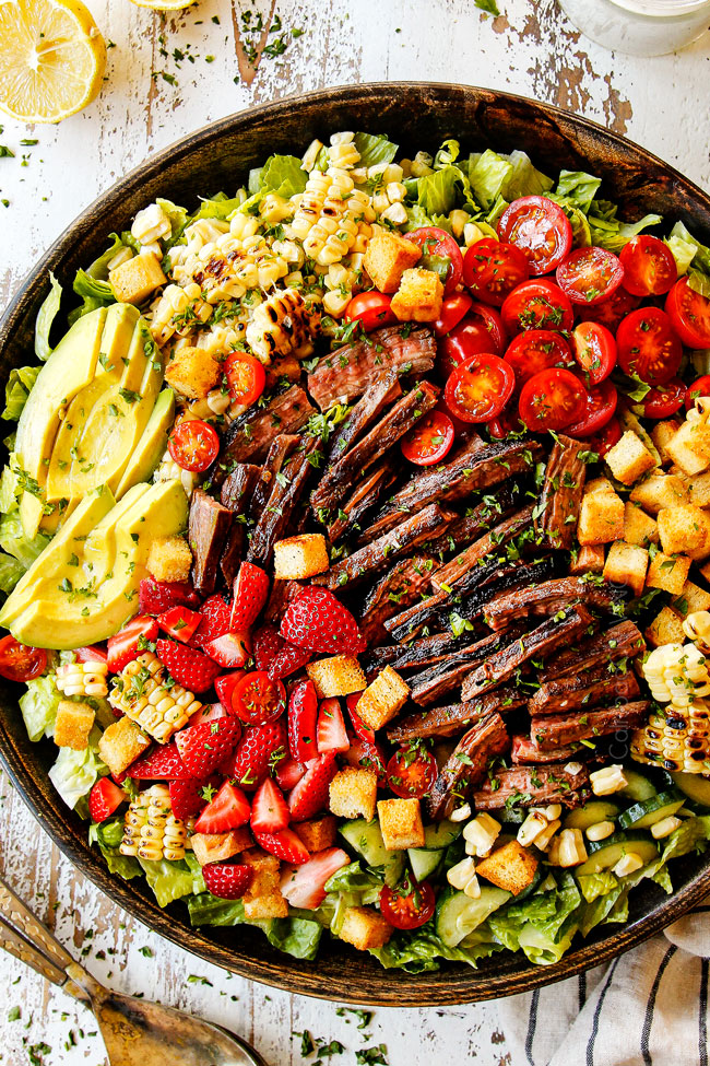 top view showing how to serve steak salad recipe by layering Romaine lettuce with grilled steak, tomatoes, corn, croutons, avocados, cucumbers and strawberries