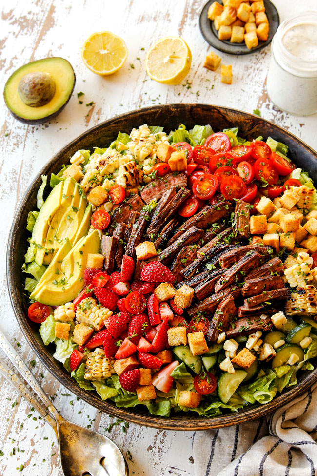 making steak salad by adding lettuce, steak, cucumbers, corn, tomatoes, steak and blue cheese to a wooden bowl