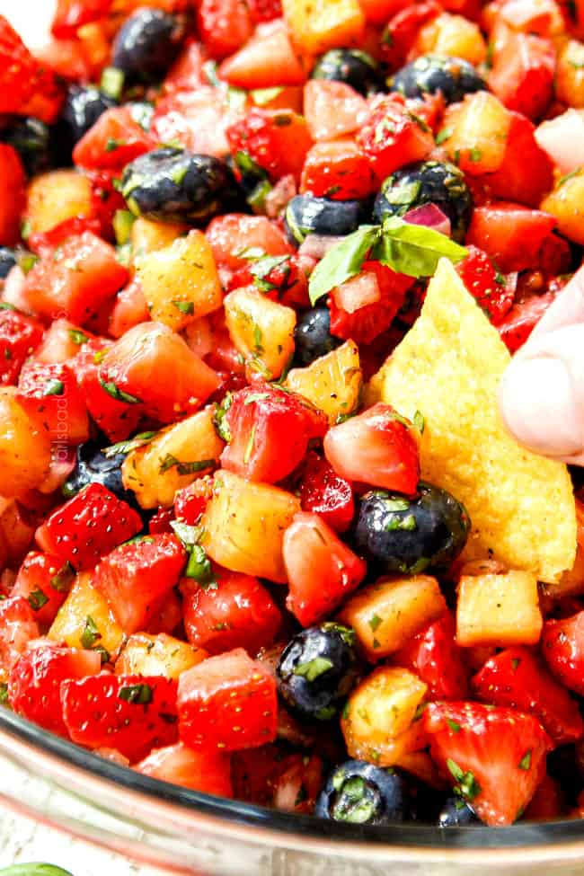up close showing how to eat strawberry salsa by scooping it up with a tortilla chip