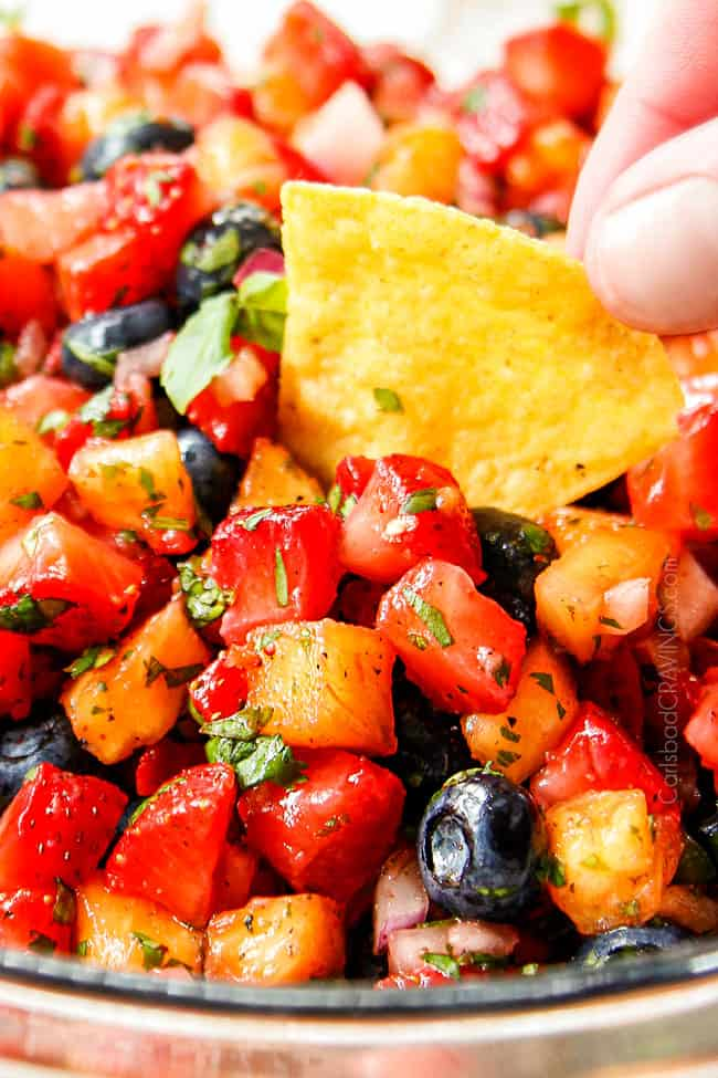 up close dipping a tortilla chip into strawberry salsa