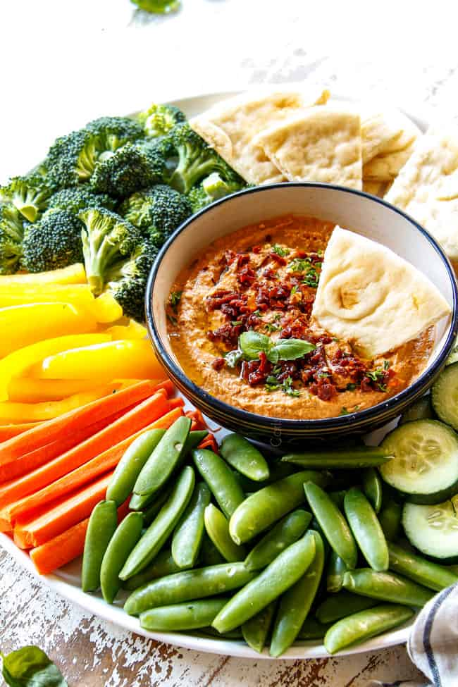 side view showing homemade hummus recipe variation of sun-dried tomato hummus in a black bowl surrounded by snap peas, carrots, yellow bell peppers, broccoli and pita bread wedges