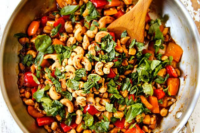showing how to make Thai basil chicken recipe by adding basil to chicken, bell peppers and sauce in a stainless steel skillet