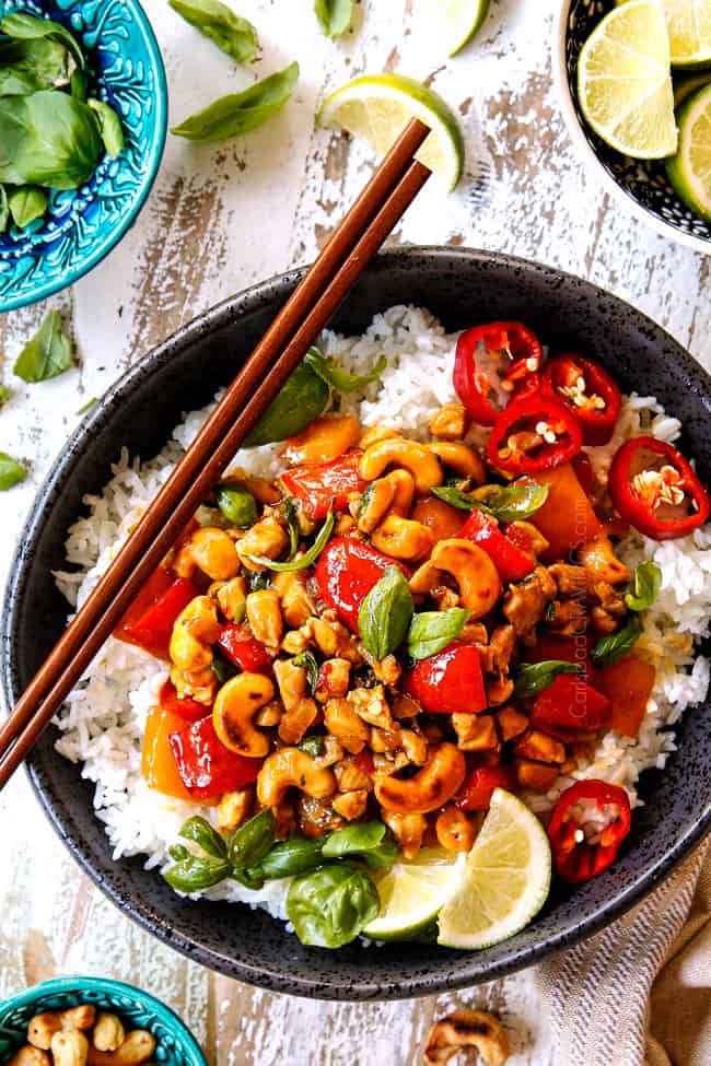 showing how to serve Thai basil Chicken recipe by adding to a bowl of white rice and garnishing with lime wedges and basil