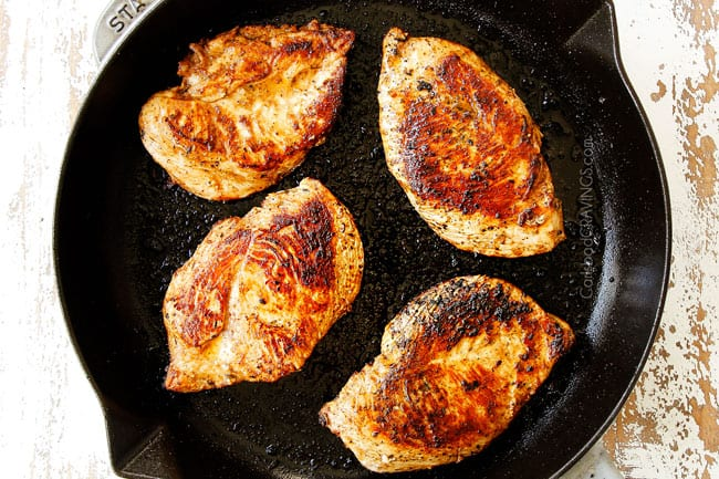 showing how to make Tuscan Chicken recipe by searing breasts in a cast iron skillet