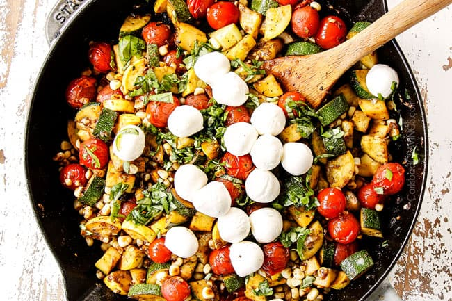 showing how to make Tuscan Chicken by adding fresh basil to the tomatoes, zucchini and corn in a cast iron skillet