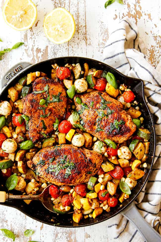 top view of Tuscan Chicken recipe with a big spoonful of veggies and chicken in a cast iron skillet