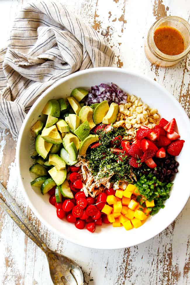 top view showing how to make avocado chicken salad by adding shredded chicken, avocados, corn, black beans, cilantro, red onions, strawberries, mangos and tomatoes to a white bowl