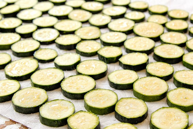 showing how to make zucchini casserole by salting zucchini slices