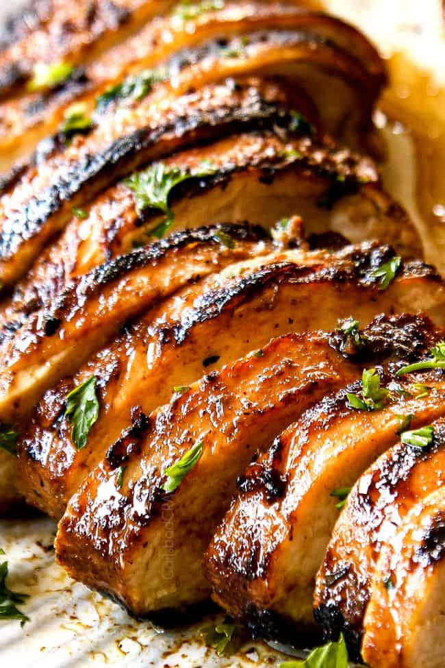 up close of marinated balsamic chicken breasts sliced on a white plate
