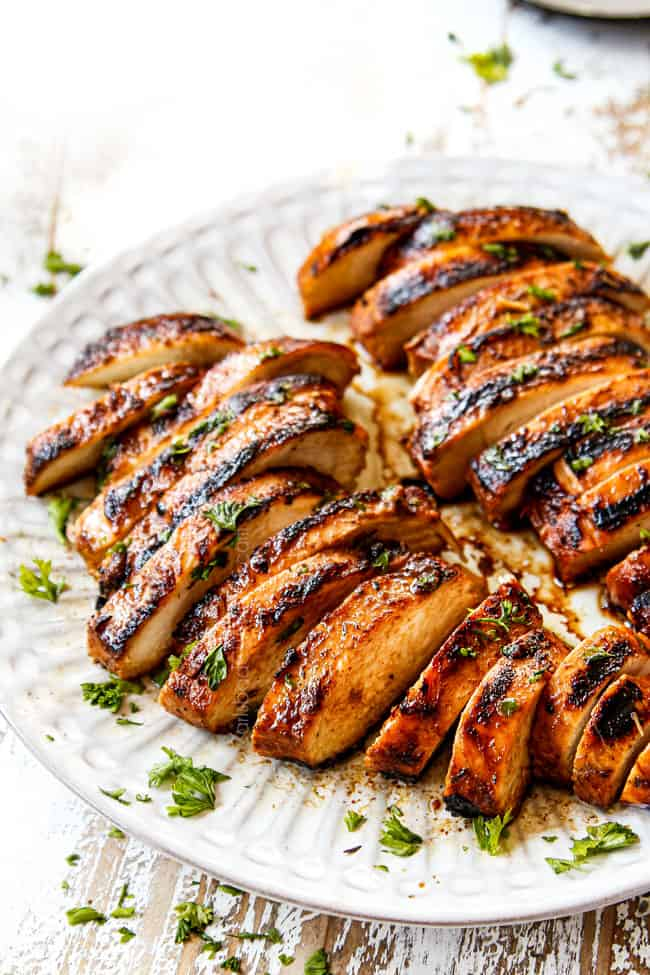 two marinated balsamic chicken breasts on a plate garnished by parsley