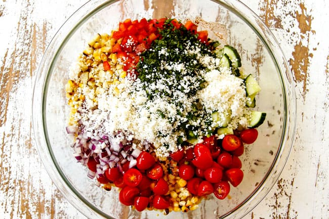 showing how to make Mexican Street Corn Salad (esquites) by combining grilled corn, red bell peppers, tomatoes, cucumbers, red onion, cilantro and Cotija cheese in a glass bowl