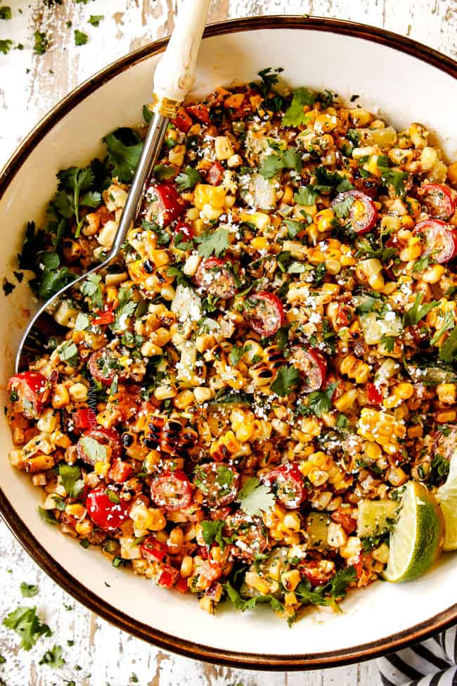 top view of Mexican Street Corn Salad (esquites) in a white bowl with a silver serving spoon