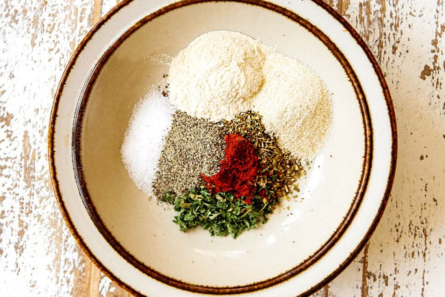 showing how to make Parmesan crusted chicken recipe by adding dried basil, dried parsley, dried oregano, salt, pepper and paprika to a bowl