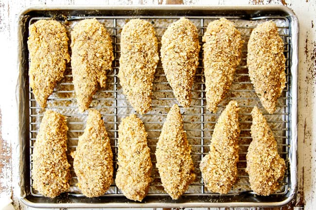 showing how to make Parmesan crusted chicken recipe by lining chicken in single layer on a baking sheet