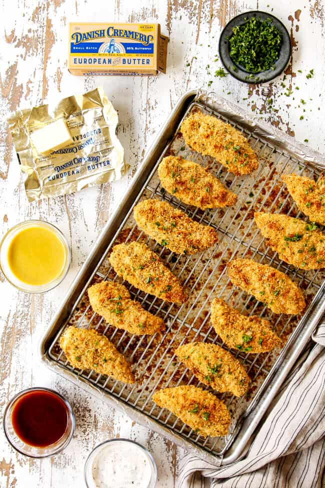 showing what to serve with baked Parmesan crusted chicken with bowls of honey mustard dip, barbecue sauce and ranch next to chicken on a baking tray