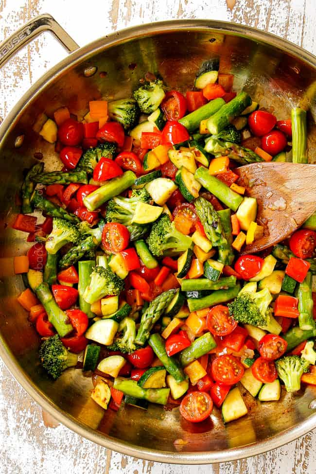 showing how to make pasta primavera by cooking broccoli, bell peppers, asparagus, zucchini and squash in a stainless steal skillet,