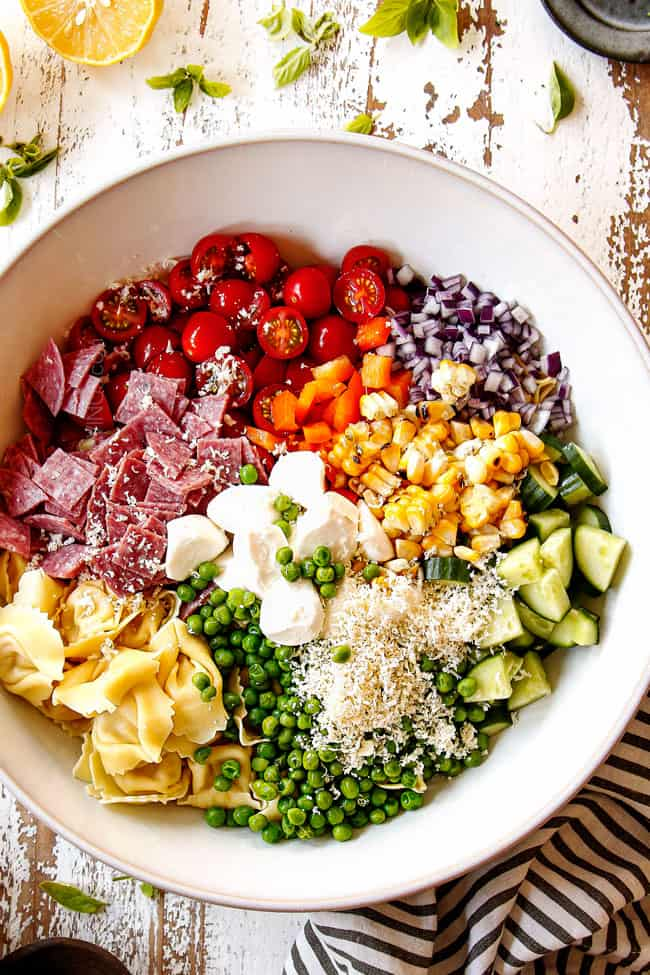 top view showing how to make pesto pasta salad by adding pasta, cherry tomatoes, mozzarella, Parmesan, cucumbers, corn, bell peppers and red onions to  white bowl