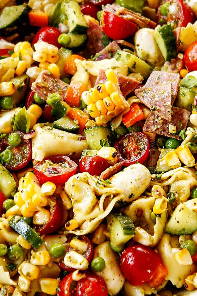 up close of pesto pasta salad with  mozzarella, tomatoes and peas in a white bowl