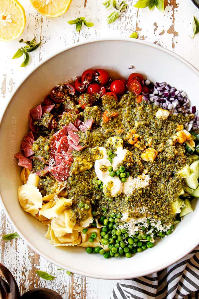 top view showing how to make pesto pasta salad by adding pesto dressing to the salad
