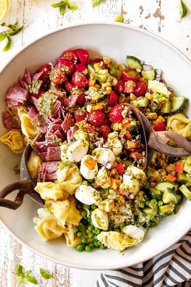 top view showing how to make pesto pasta salad recipe by tossing the ingredients with the pesto dressing in a white bowl