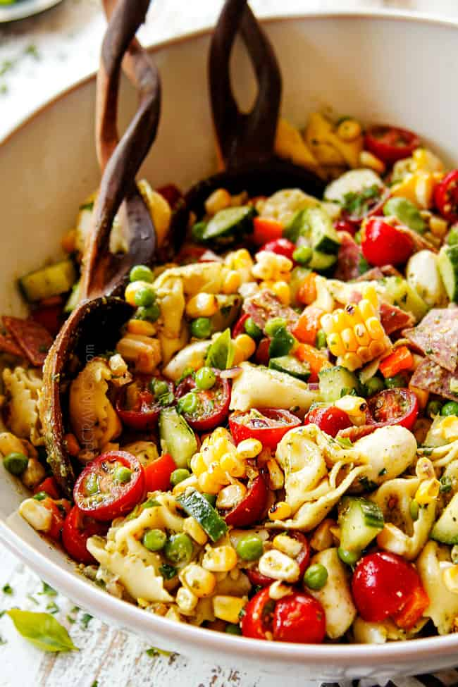 side view of pesto pasta salad recipe with vegetables in a white bowl with wooden tongs