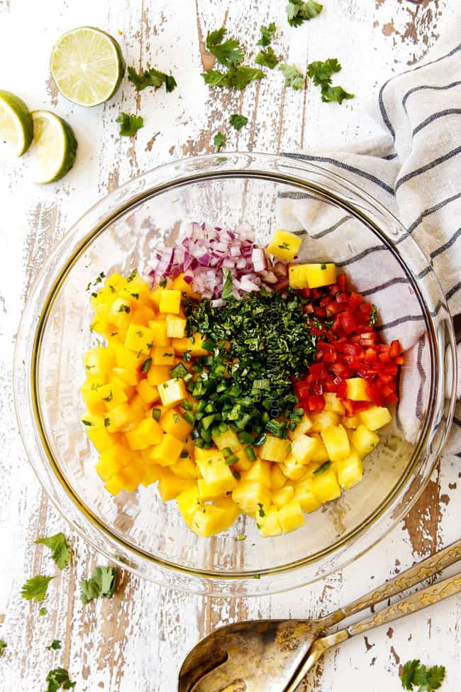 showing how to make top view of pineapple mango salsa by adding pineapple, mangos, red onions, red bell peppers, cilantro and jalapeno to a glass bowl