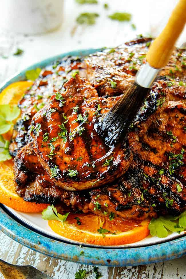 brushing reserved pork chop marinade on grilled pork chops