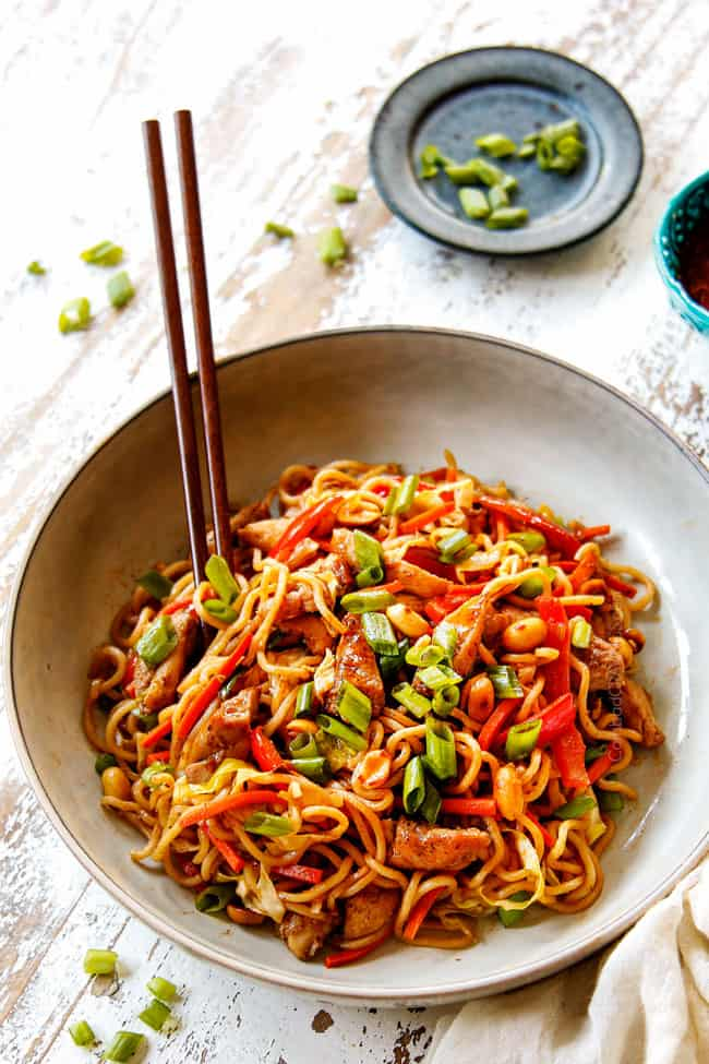 showing how to serve yakisoba recipe by adding to a white bowl with green onions and chopped sticks