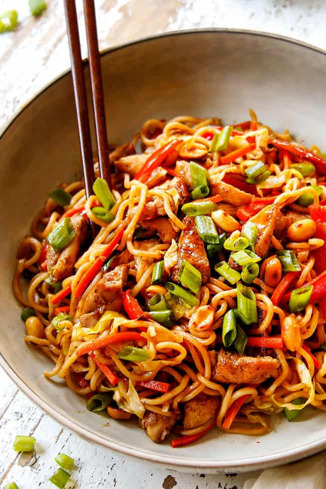 up close of yakisoba in a white bowl with chopsticks garnished with green onions
