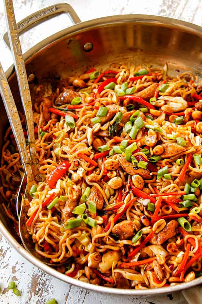 showing how to make chicken yakisoba by tossing yakisoba noodles with yakisoba sauce and green onionsv