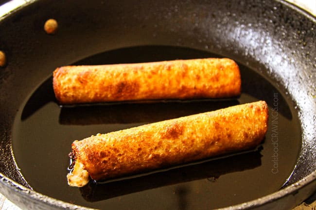 showing how to make flautas by frying flautas in a black skillet