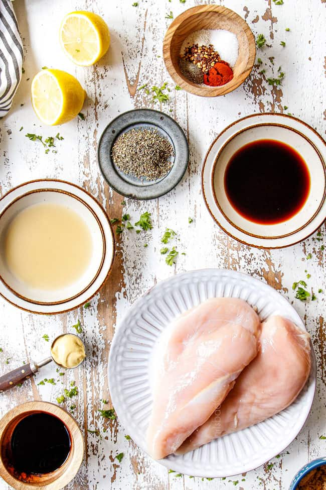 top view of showing how to make grilled chicken marinade by laying out ingredients in bowls: balsamic, lemon juice, Dijon, oregano and ketchup and chicken breasts on a white plate