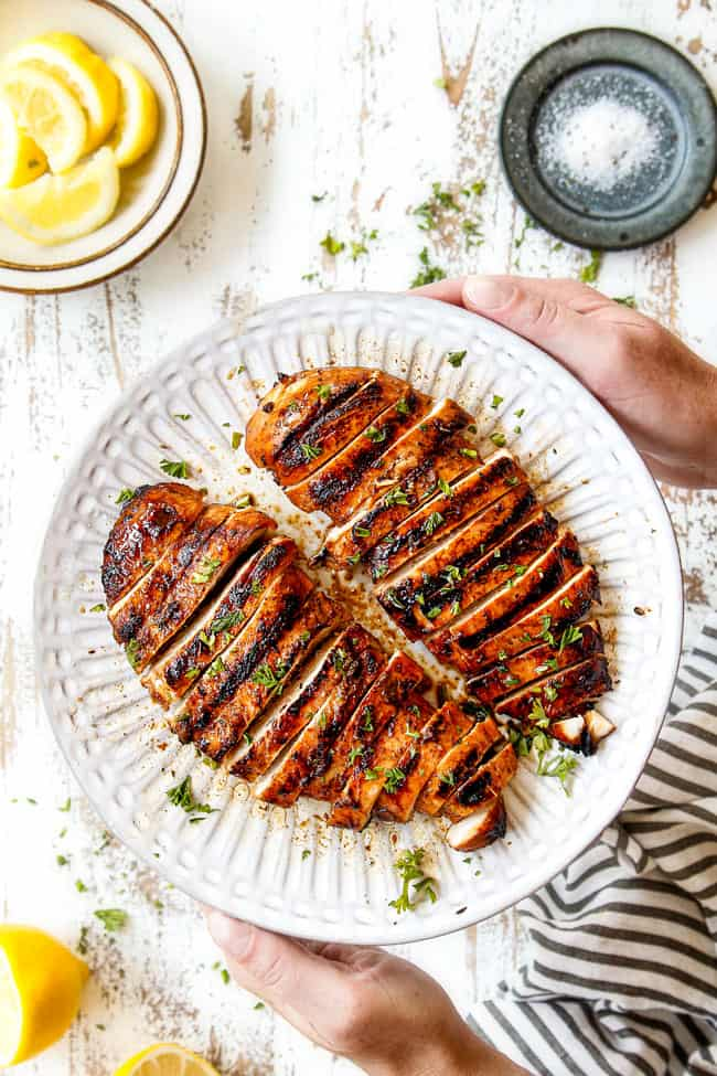 top view of marinated grilled chicken breasts sliced on white plate being held by two hands