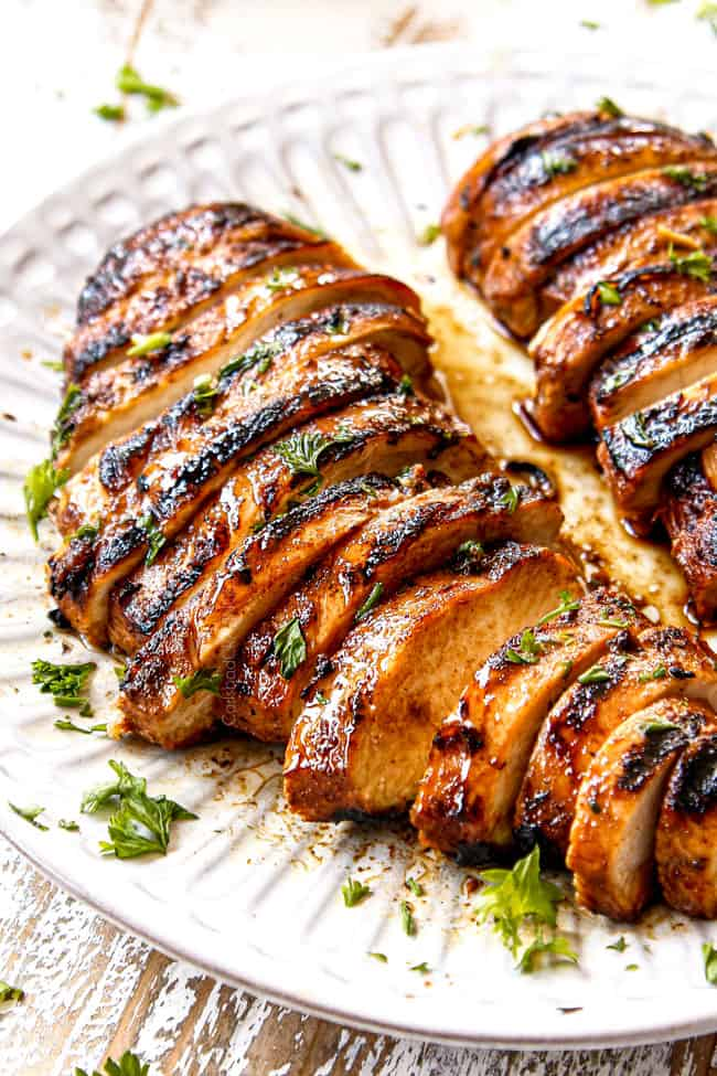 side view of marinated grilled chicken breasts sliced on white plate
