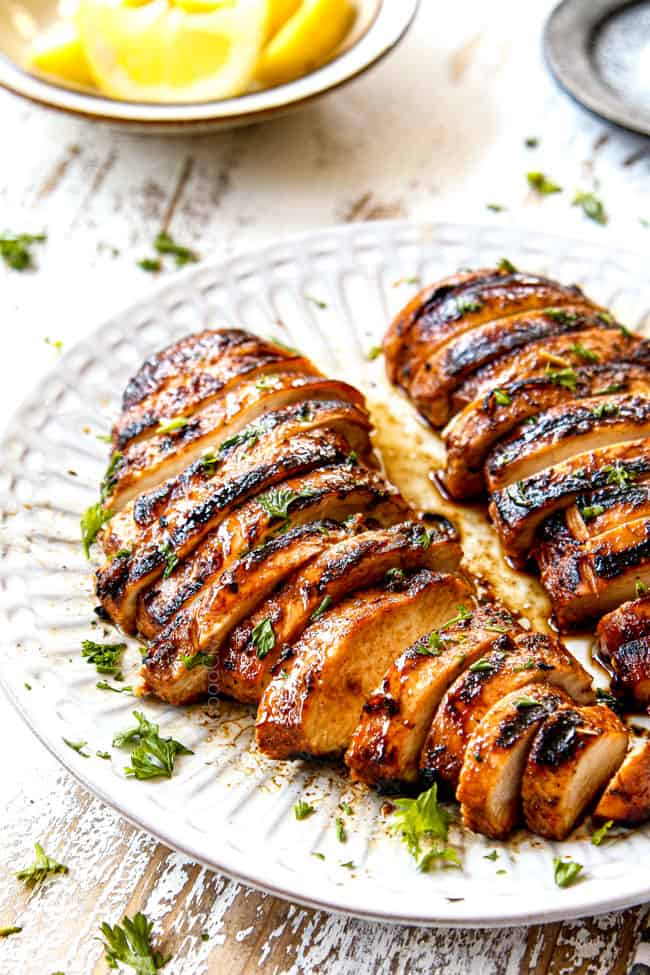 side view of the best marinated grilled chicken on a white plate garnished with parsley