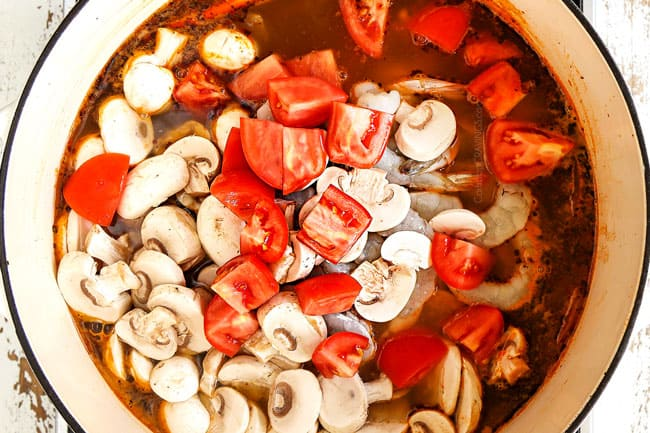 showing how to make Thai Tom Yum Soup recipe by adding shrimp, tomatoes and mushrooms to the soup pot