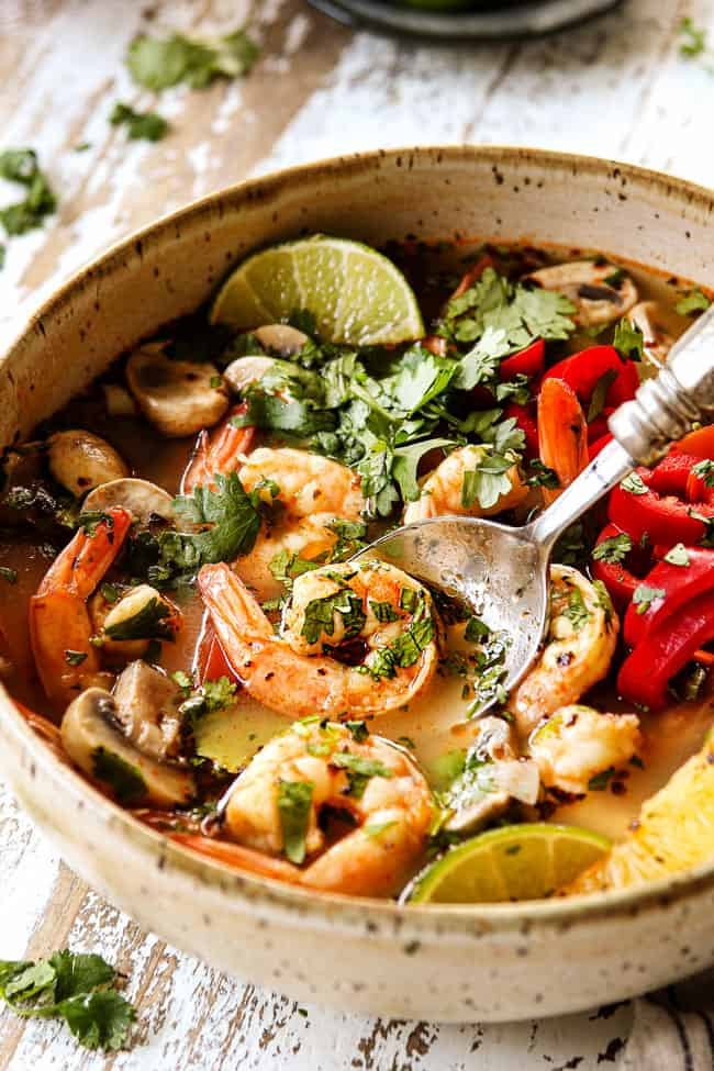 up close of a bowl of Tom Yum Soup recipe with a spoon scooping up shrimp