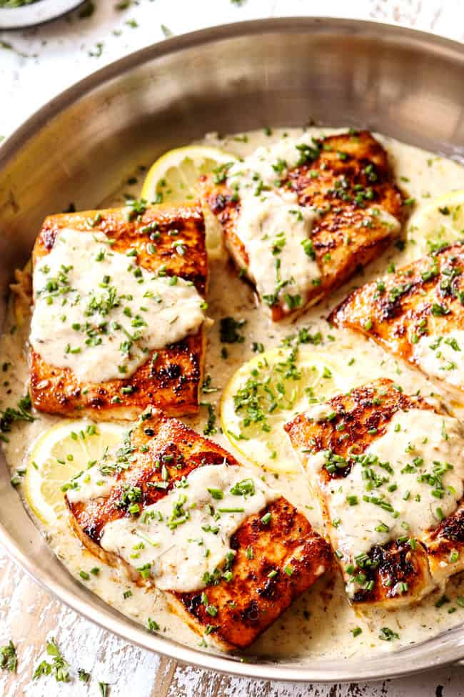 mahi mahi fish in a stainless steel skillet with lemon cream sauce garnished by chives
