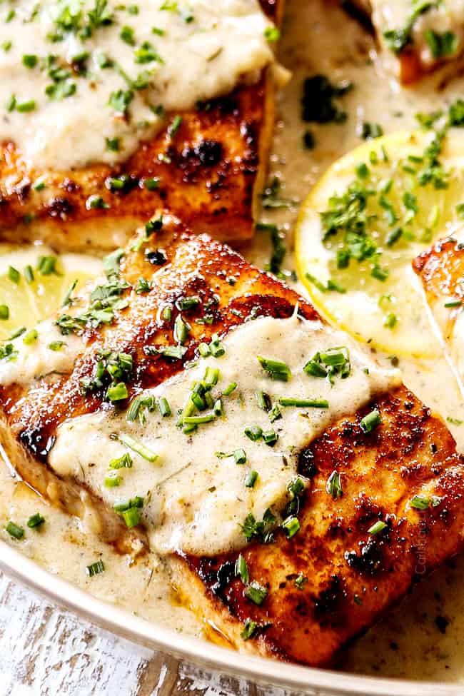 up close of mahi mahi fish garnished with parsley and chives in lemon cream sauce