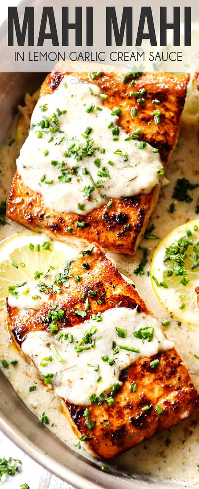 up close view of mahi mahi  on a stainless steel skillet with lemon cream sauce