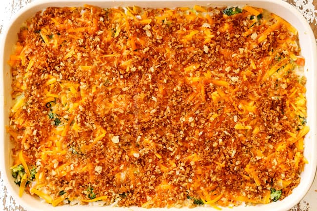 showing how to make chicken broccoli and rice casserole by topping a 9x13 with shredded cheddar followed by panko
