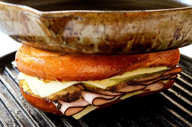 showing how to make Cuban sandwich recipe by toasting the Cubanos on a griddle pan and pressing down with a heavy skillet