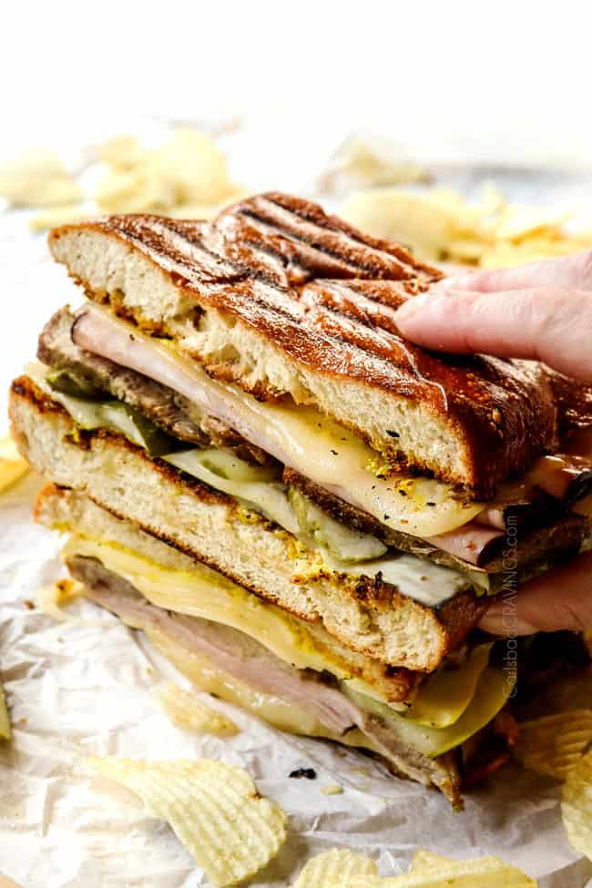 a hand picking up a Cubano sandwich (Cubano) with Swiss cheese, mojo pork, ham, pickles and mustard