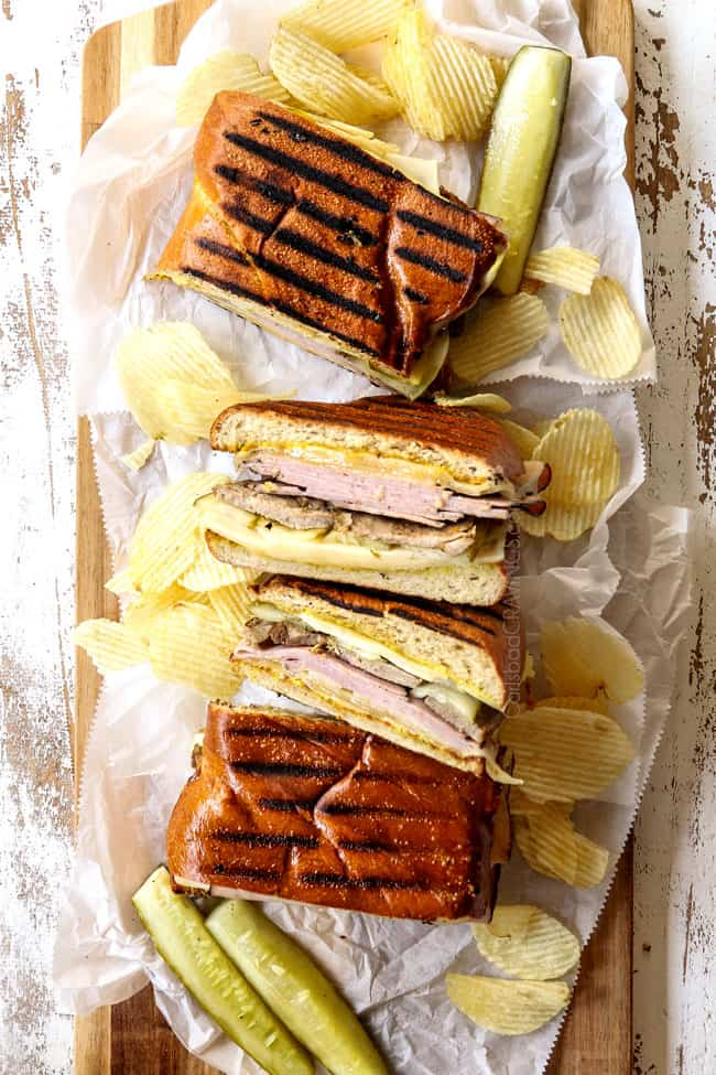 four Cubano sandwiches (Cubanos) on a a wood platter surrounded by potato chips