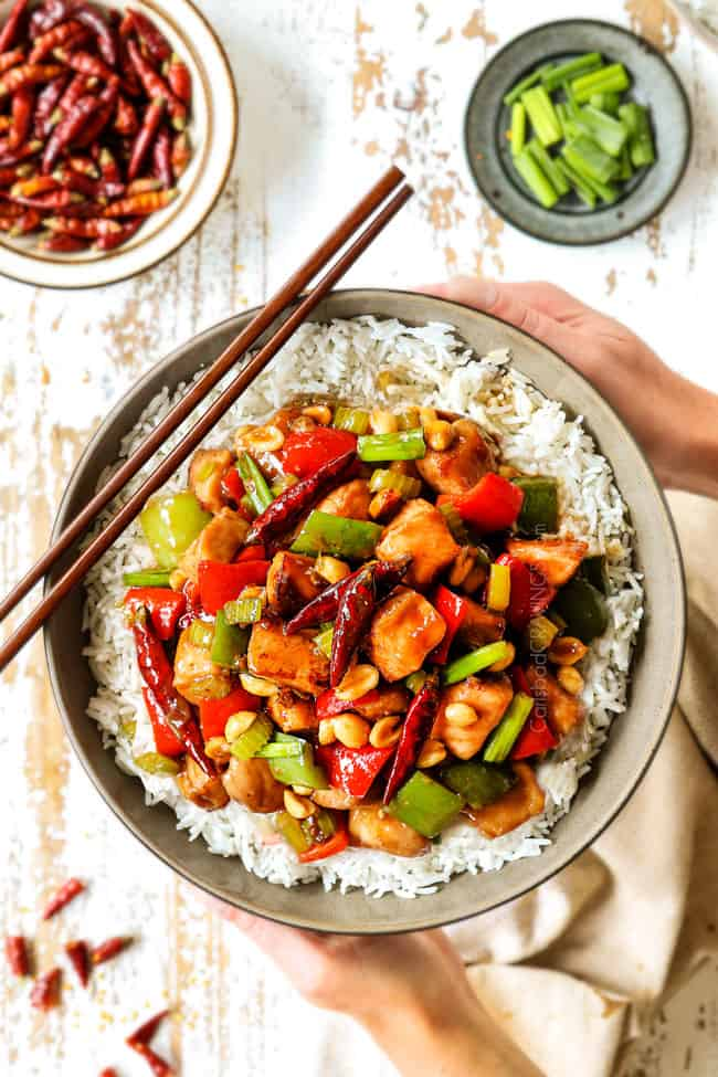 showing how to serve best kung pao chicken recipe by holding chicken in a bowl with rice and chopsticks