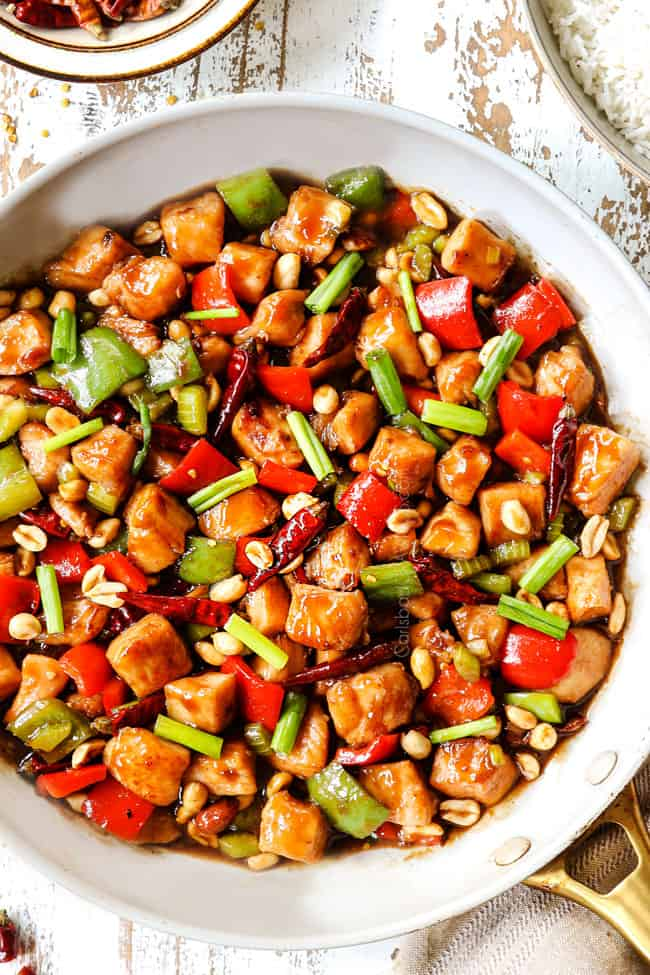 top view of easy kung pao chicken in a white skillet garnished with green onions