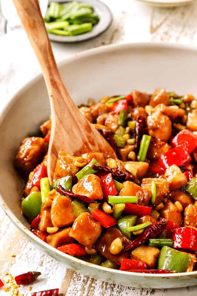 a wooden spatula serving best kung pao chicken form a white skillet