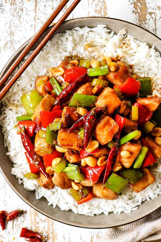 top view showing how to eat kung pao chicken by adding to a bowl of rice, garnishing with green onions and peanuts