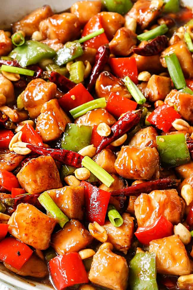 up close of best kung pao chicken recipe in a white skillet showing how juicy the chicken is